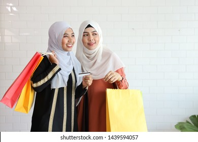 young muslim girls pointing at something and holding shopping bags and credit card on white background