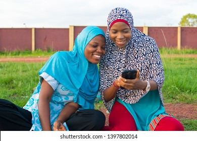 young muslim girls viewing something on a phone together outdoor