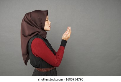 Young muslim malay girl praying with hand gesture isolated on grey background.