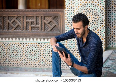 Young Muslim man in casual clothing smiling and working on tablet in traditional Arabian ambient