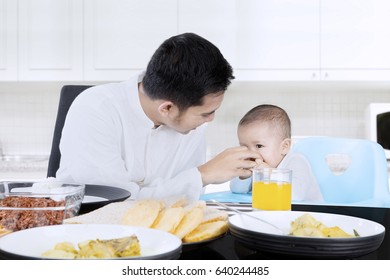 Young muslim man feeding his female baby with hand on the table at home