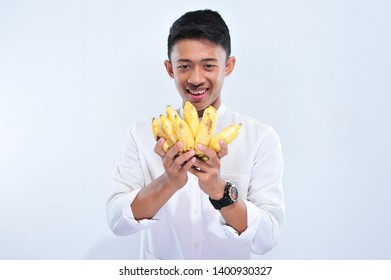 Young muslim man happy fasting when breaking the fast (Iftar) and suhoor eat yellow banana islolated in white background