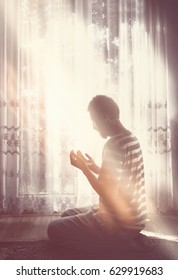 Young muslim man have a pray time with hands up in the air dua pose. Light beams comming from heaven bright window.