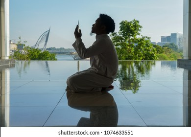 Young Muslim man performing pray in Islamic attire.
