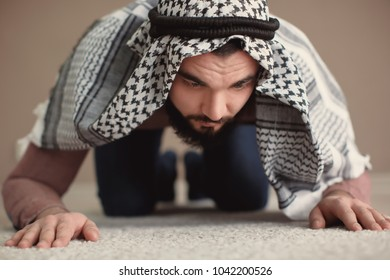 Young Muslim man praying, indoors