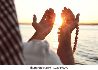 Young Muslim man praying near river at sunset