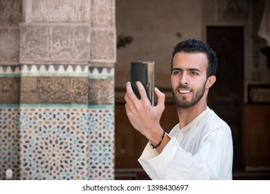 Young Muslim man in traditional clothing smiling and taking selfie with mobile phone