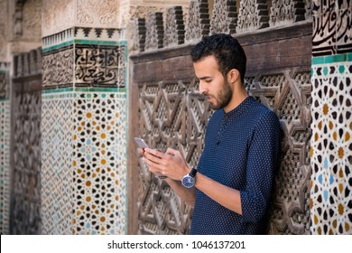 Young Muslim man using his mobile phone in casual clothing beside the wall with traditional Moroccan arabesque decoration
