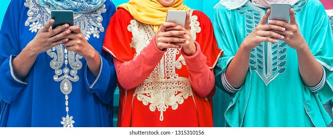 Young Muslim people using their mobile smart phones in the college - Arabian girls addicted to new technology app cellphone for social media - Millennial, religion, generation z and technology concept