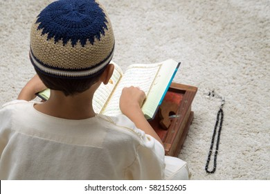 Young muslim reading Al Quran during fasting month of Ramadan.