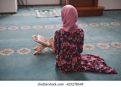 Young Muslim reads the Koran, sitting in the direction of the Qibla, hands on knees, ending prayer, witness, prayer Rukn, back to me