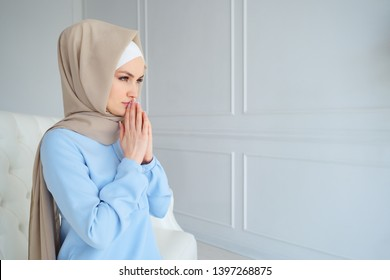 young muslim woman in beige hijab and traditional clothes praying for Allah, copy space.