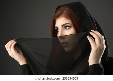 Young muslim woman covering her hair and face with a black veil