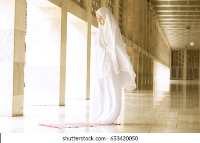 Young muslim woman doing salat in the mosque