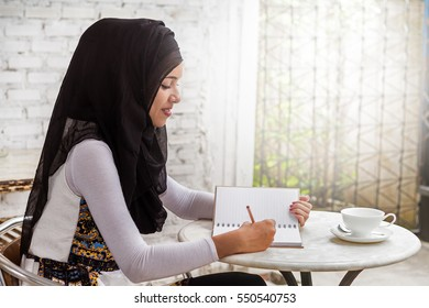 Young Muslim woman in head scarf with modern clothes with pen writing on notebook.