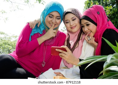 young muslim woman in head scarf take a photo with friends