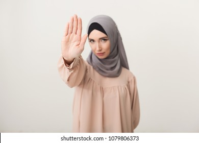 Young muslim woman in hijab doing stop gesture at studio background. Stop abuse and denial concept, copy space
