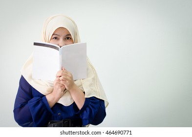 Young muslim woman holding book in front of her face with blank area for sign or copyspace.  Concept for education, project, proposal, research, study, business