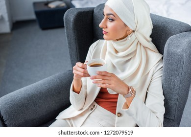 young muslim woman holding cup of coffee and looking away at home