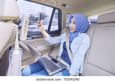 Young muslim woman with a laptop computer, taking selfie photo with mobile phone in the car