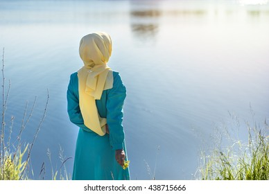 Young muslim woman outdoors portrait. waiting on the river bank