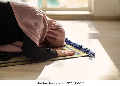 Young Muslim woman praying at home