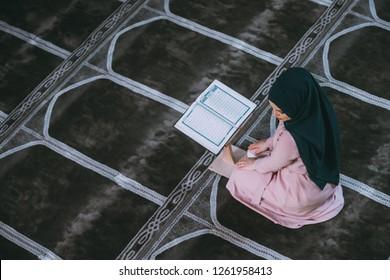 Young muslim woman praying in mosque