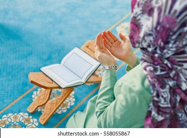 Young muslim woman praying in mosque with Quran - the holy book of Islam