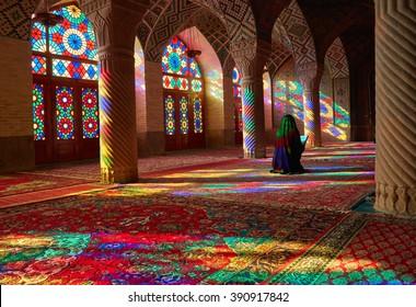 Young Muslim woman praying in Nasir Al-Mulk Mosque (Pink Mosque), Iran, Shiraz