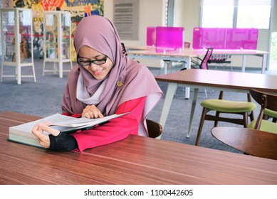 Young Muslim woman reading a book. Muslimah concept.