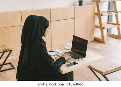 young muslim woman using laptop with blank screen in cafe
