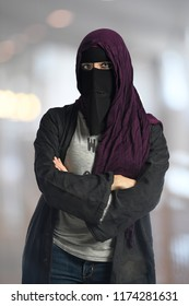 Young Muslim woman wearing nigab and headscarf with arms crossed inside building