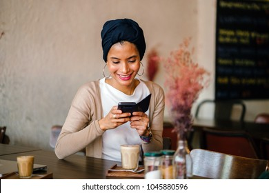 A young Muslim woman wearing a turban taking photographs of her coffee and food. She is smiling as she documents her meal for social media.