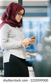 A young Muslim woman wearing a turban (hijab) is working on her phone by standing in office. She is elegant, beautiful and professional.