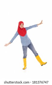 Young muslimah wearing yellow boot in pose