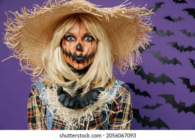 Young mysterious woman 20s with Halloween makeup mask in straw hat scarecrow costume spread hands say booo isolated on plain dark purple background studio portrait Celebration holiday party concept