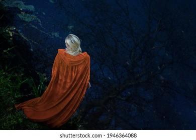 junge rätselhafte Frau in gelbem Oper mit Kapuze. Zug und langes blondes Haar. Rückseite des Assistenten.