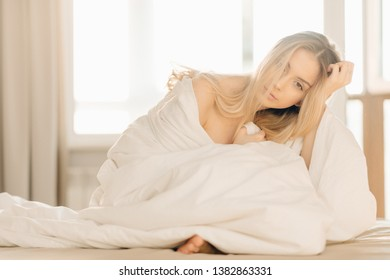 Young naked blonde woman sitting in bed in the morning. Tenderness, charm, beauty. Happy pleased woman covering herself with a blanket.