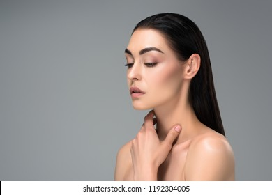 young naked brunette woman touching neck with hand and looking away isolated on grey