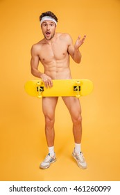 Young naked confused sports man holding skateboard isolated on a orange background