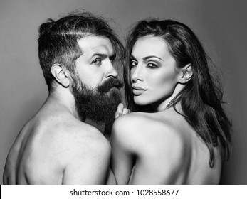 young naked couple of sexy woman with makeup on pretty face and brunette hair with bare shoulders on body back and handsome bearded man with long beard in studio