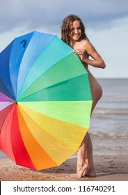 Young naked girl with a colorful umbrella on the beach