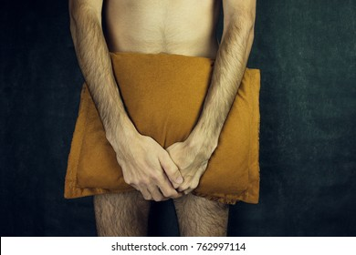 Young naked man is covering his penis with  pillow.