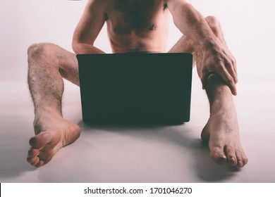 Young naked man watching pornography and masturbating
