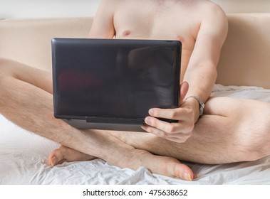 Young naked man is watching pornography on laptop and masturbating.
