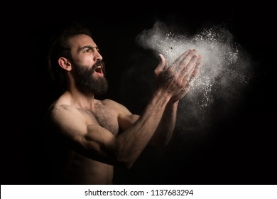 Young naked sporty bearded man clapping hands with chalk powder, preparing for weightlifting training, in a dark background.