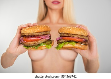 Young naked woman keep in her hands two tasty burgers.