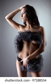 Young naked woman stand and close breast by fur