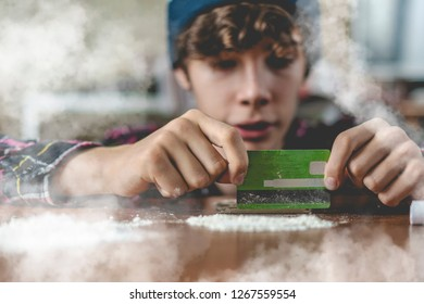 young narcotic junkie prepare and chop cocaine lines on the wooden table