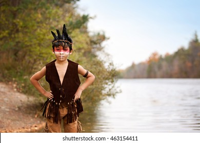 Young Native American.  Adorable young boy dressed as a Native American standing by the shoreline.
